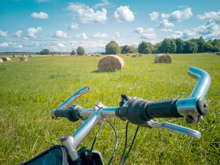 Bicycle first person view from camera. Bike In The Country Side. Travel concept. Mountain bike on summer field background. Sportive lifestyle 写真素材