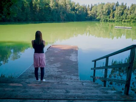 Female photographer on wooden pier taking a photo of landscape of a lake with green water with forest background. In concept travel alone. Traveling Holiday camera girl 免版税图像