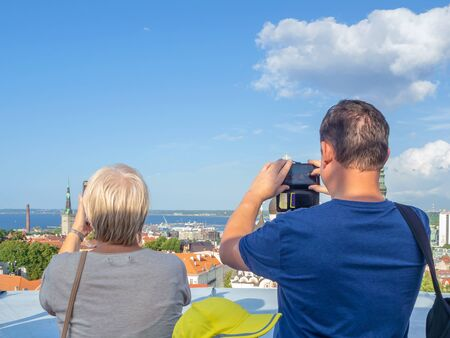 Tourists are taking a photo of landscape on the roof. The bell tower of St. Nicholas  Church. Tallinn city. Estonia. Aerial top view of the old town from Tall Hermann observation platform