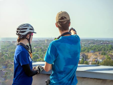 Middle age mature cyclist man and young boy wearing safety helmet Pointing ahead the direction of travel On bicycles. Green trees and city on the background. View from the observation deck