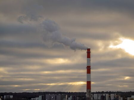 Stock Photo - Big industrial red and white pipe with smoke going outside. Toxic smoke pollutes the atmosphere. Factory pipe polluting air, environmental problems. Dark clouds on the background. Toning Stock Photo