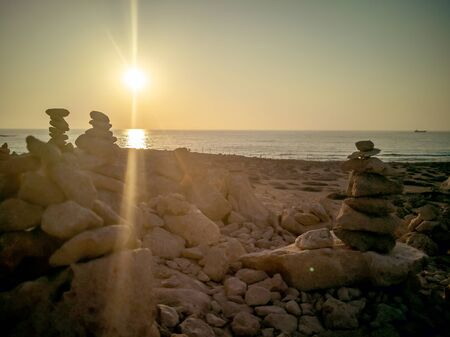 Stone pyramides at Tombs of the kings on Paphos, Cyprus. Stones laid out in shape of pyramid on background of Mediterranean sea. ancient Archaeological Park. Sunset. Copy space. Filtered image