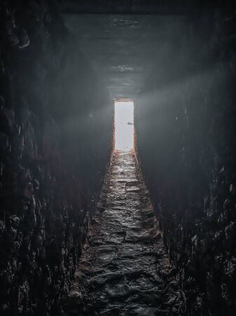 Light and exit in the end of dark long tunnel or corridor, way to freedom concept. Industrial round chalk mine passage With hole, perspective, toned