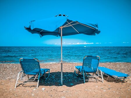 Sunbeds and umbrella on sea beach with sand on the background of sea and blue clear sky. Summer vacation on tropical. Tourism and beach concept. Cyprus Beach. sandy shore. Accessories