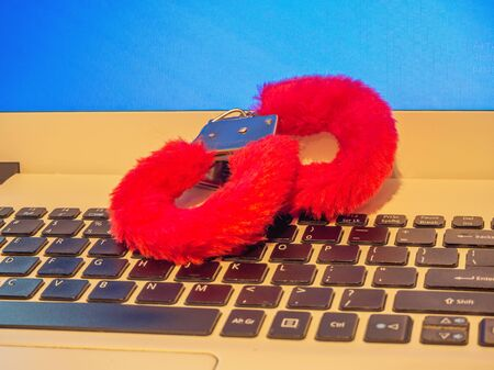 fluffy pink handcuffs on the computer. Love concept. Filtered image. Copy space Stock Photo
