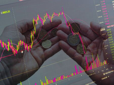 two hands with euro coins. Technical price graph and indicator, red and green candlestick chart on black screen, market volatility, up and down trend. Stock trading, currency. Market Crash concept Stock fotó - 142645945