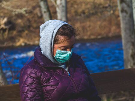 Lady and coronavirus protection. Sad Woman sitting alone on bench in park wearing mask to avoid infectious. Corona virus, or Covid 19, is spreading all over the world. Receives bad news on her phone.