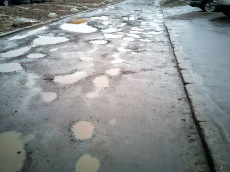 Water erosion of road. Broken asphalt of a big city. Danger hole. Lumpy, pavement. broken road in Russian. Hole in the asphalt, risk of movement by car, dangerous road, pit unsafe hole road concept