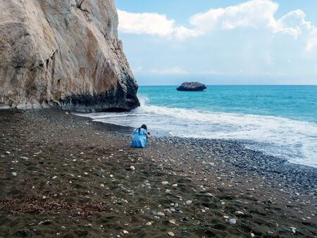 Young beautiful girl take photo on the Love beach. Aphrodites Rock is a birthplace near Paphos City. The rock of the Greek - Petra tou Romiou. Cyprus island