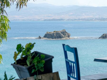 High table and chairs in outdoor cafe, Cyprus with sea view on The beach of Aphrodite, famous tourist destination, Cyprus. Amazing Seascape
