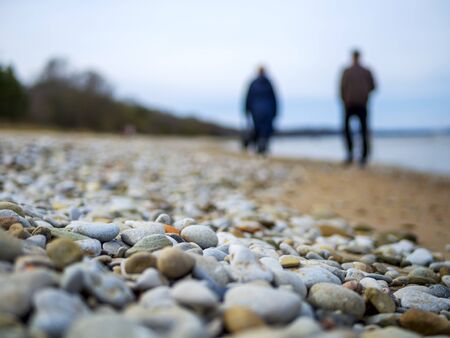 Selective focus. Coast. Spa stones, sea beach. Coast. many Stones on the beach and sea water in sunset light. people silhouette on background