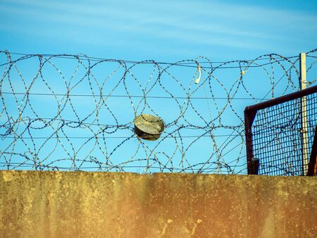 Restricted Area Barbed Fence. Concrete wall, against the backdrop of barbed wire, the concept of prison, salvation, Refugee, lonely, space for text. Protected object, no unauthorized entry.