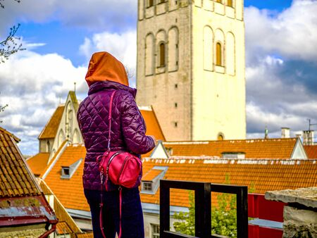 Tourist in Estonia, taking photo of old town with smartphone. Travel photography with mobile phone. travel and photography concept, young beautiful woman in red looks towards city towers. copy space