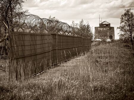 Old observation in abandoned Soviet Russian military complex. guarding tower, fence with barbed wire. Copy space. toned image