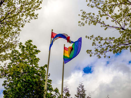 LGBT and Holland flags on poles blow in the wind. Symbol of tolerant. Gay sign rainbow. The rainbow pride, Trees and blue cloudy sky on the background. Copy space