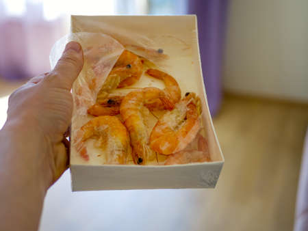 paper packaging filled with fresh shrimps in man hands. window on the blurred background. Food for diet - Grilled shrimps with mango salad. Home cook in Asian kitchen.