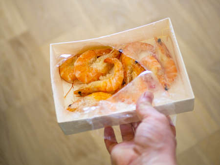 paper packaging filled with fresh shrimps in man hands. brown floor on the blurred background. Food for diet - Grilled shrimps with mango salad. Home cook in Asian kitchen.