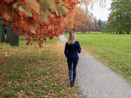 Selective focus. Blurred background. Backview of girl walking in the city park. Outdoor autumn portrait of young womann standing backwards with straight blond hair. forest nature at fall.