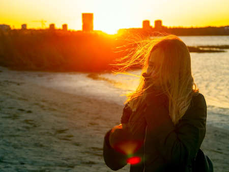 Silhouette of a lonely woman watching sunset in autumn. downtown buildings silhouettes. Nature Orange sea sunset in the city landscape beautiful landscape of Tallinn skyline Panoramic view on beach