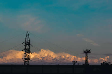 Electricity pylons, power lines and trees silhouetted against a cloudy sky at sunset. Imagens