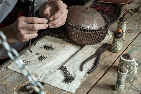 Master weaves chain mail from metal rings. Dragon scales. Tools for making chain mail.