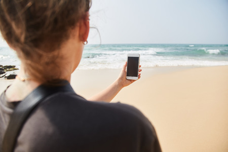Mobile phone in female hand on the background of the beach and ocean. A young girl makes a photograph of the ocean. Close-up. Sri Lanka.