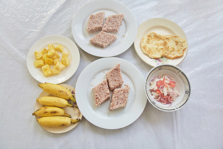 National cuisine of Sri Lanka. Rice cooked in coconut milk. Bananas. Sliced pineapple. Omelet. Tomato and onion salad. Kiribath