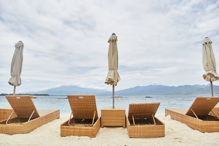 Sun beds with umbrellas on the Bali beach.