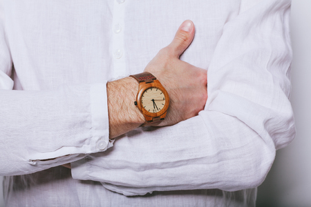 A man in an elegant white shirt with a clock on his hand. 写真素材