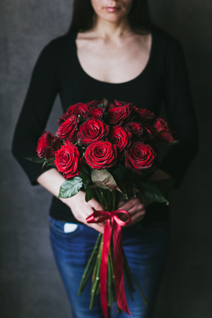 Bouquet of red roses in the hands of a woman. 写真素材 - 123634244