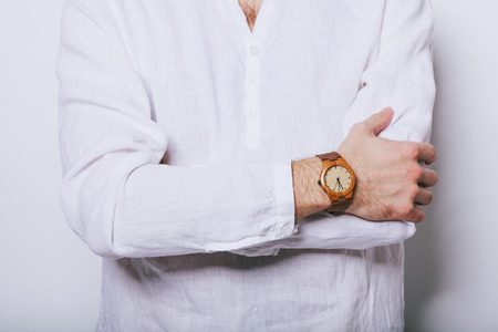 A man in an elegant white shirt with a clock on his hand. 写真素材 - 124716442