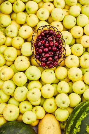 Yellow ripe apples, pile of fresh apple fruits, basket with cherries.