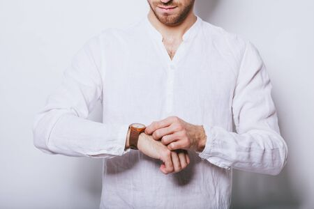 A man in an elegant white shirt with a clock on his hand. Banco de Imagens