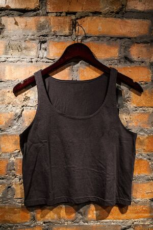 Black blank t-shirt hanging on a red brick wall. Mock-up.