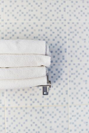 A stack of white clean towels in a hotel room. White towels lie on a shelf in the hotels washroom