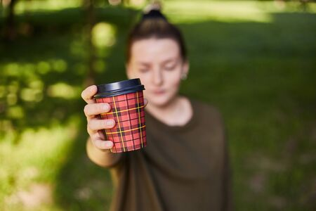 Young girl holds a glass with coffee in the foreground