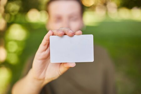 Girl holding a white credit card in her hands for shopping. Close-up Stock Photo