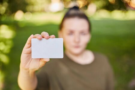 Girl holding a white credit card in her hands for shopping. Close-up