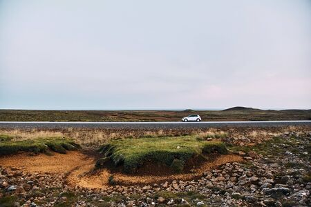 Grey car stands near a road in Iceland.