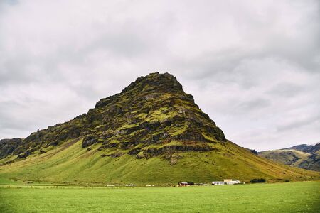 Mountain near Eyjafjallajokull volcano area in Iceland. Green field, blue sky, sunny summer day.