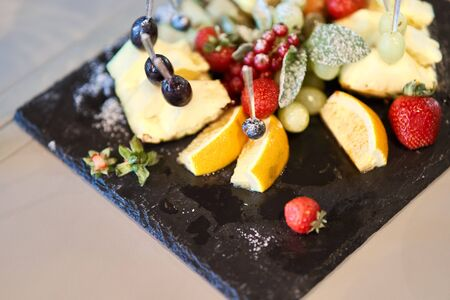 Fruit sliced on a stylish plate. Pineapple, pear, orange, apple, grape, wild strawberry 写真素材