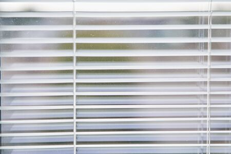 Closeup view of window with horizontal blinds. White Roller Blinds or Louver curtains at the glass window