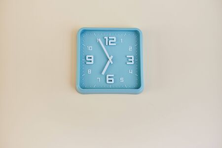 Turquoise clock hanging on a white wall. 写真素材