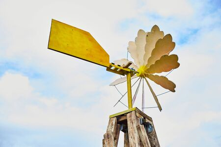 Old wooden windmill against a blue sky.