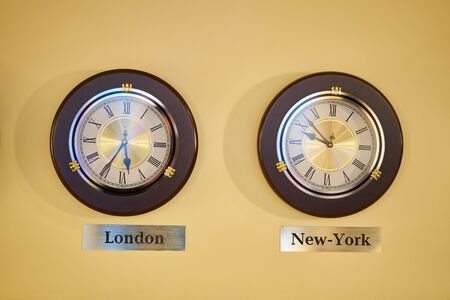A wall clock showing the time difference between London and New York. Time zones on a watch.