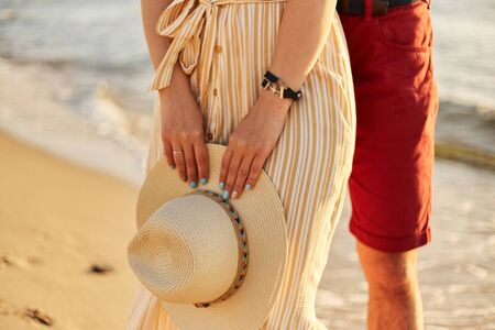 A straw hat in the hands of a girl. Walk along the beach.