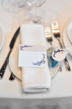 Napkin on plates with the name of the guest. Serving a guest seat at a wedding. Table decoration. Wedding celebration. Banquet in the restaurant. Wedding organisation. Stock Photo