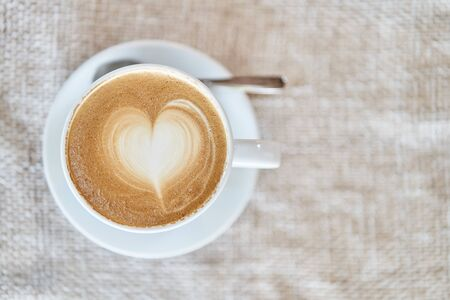 Top view of a mug with latte on a brown background. Coffee with a heart shape.