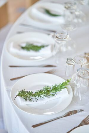 Wedding decorations. White plates on a white tablecloth. Natural style wedding. Stock Photo