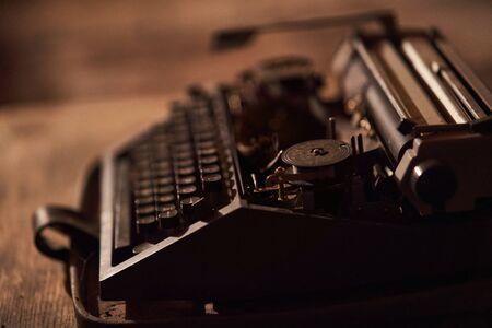 Vintage old black typewriter closeup. Standing in an old brick basement 스톡 콘텐츠